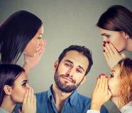 Vier Frauen, die einen geheimen Klatsch zu einem gebohrten gestörten Mann flüstern stockfoto