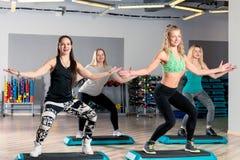 vier Frauen nehmen an Aerobic in der Turnhalle teil Lizenzfreie Stockbilder