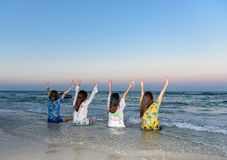 Vier Frauen waren die Freunde, zurück gesessen und hoben ihre Hände auf dem Strand an stockfotos
