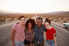 Vier Freunde auf einer Wüstenlandstraße oben lächelnd zur Kamera, Abschluss lizenzfreie stockfotos