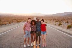 Vier Freunde, die auf einer Wüstenlandstraße lächelt zur Kamera stehen lizenzfreie stockfotos
