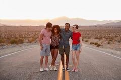 Vier Freunde, die auf einer Wüstenlandstraße schaut zur Kamera stehen stockbilder