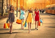 Vier Freunde, die das Einkaufen tun stockfotografie