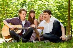 Vier Freunde, die durch Gitarre singen Lizenzfreie Stockfotografie