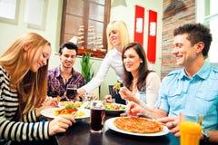 Vier Freunde, die an einem Restaurant zu Mittag essen Stockbild