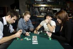 Vier Freunde, die Schürhaken spielen Stockbild