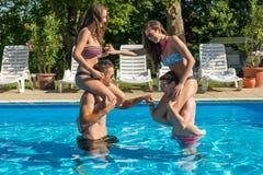 Vier Freunde, die Spaß im Swimmingpool haben lizenzfreie stockbilder