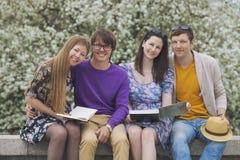 Vier Freunde im Park mit Büchern Stockfoto
