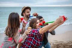 Vier Freunde mit roten Nasen nehmen ein selfie und feiern einen Geburtstag auf dem Strand stockfotos