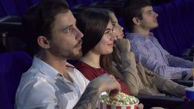 Vier Freunde sitzen in der Kinohalle und passen den Film auf stockfotos
