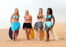 Vier Freundinnen, die auf Brandungsbrettern stillstehen Stockfoto