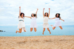 Vier Freundinnen, die auf Strand springen lizenzfreies stockfoto