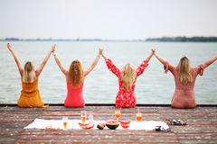Vier Freundinnen mit dem langen Haar an der Plattform lizenzfreie stockfotografie