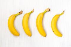 Vier frische Bananen auf Holztisch Stockbilder