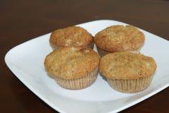 Vier frische Muffins auf weißer Platten-und Kirschtabelle Stockfotos