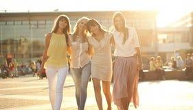 Vier frohe Freundinnen auf dem Weg lizenzfreie stockfotos
