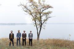 Vier gangsters bevinden zich in de herfst Drie van hen kruisten hun wapens, hield één van hen een hoed retro outdoors royalty-vrije stock fotografie
