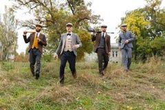Vier gangsters gaan houdend ergens een automaat en een knuppel retro outdoors royalty-vrije stock fotografie