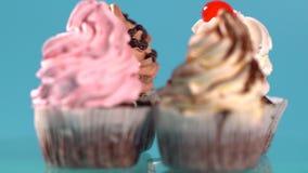 Vier geassorteerd cupcakes met getold suikerglazuur stock footage