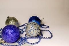Vier gekleurde glanzende Kerstmisballen liggen op de linkerzijde op een witte achtergrond royalty-vrije stock foto