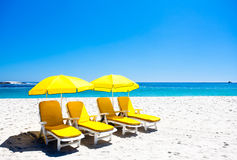 Vier gelbe Strandstühle stockfotografie