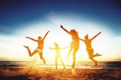Vier gelukkige die meisjes en sprong tegen zonsondergangoverzees in werking worden gesteld royalty-vrije stock afbeeldingen