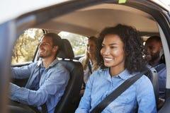 Vier gelukkige jonge volwassen vrienden in een auto op een wegreis stock foto's