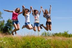 Vier gelukkige jonge vrienden die van vrouwenmeisjes hoog tegen blauwe hemel springen Royalty-vrije Stock Foto's