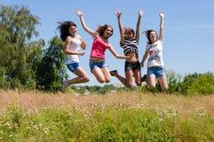 Vier gelukkige jonge vrienden die van vrouwenmeisjes hoog tegen blauwe hemel springen Stock Afbeelding