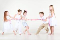 Vier gelukkige meisjes en de jongen trekken over kabel Stock Foto