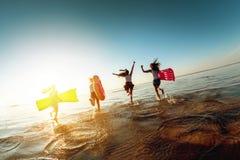 Vier gelukkige meisjeslooppas aan zonsondergangmeer stock fotografie