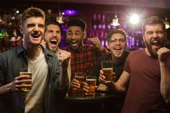 Vier gelukkige mensen die bier mokken en het gesturing houden royalty-vrije stock foto