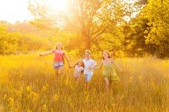 Vier gelukkige mooie kinderen die het speel bewegen samen in de mooie de zomerdag in werking stellen zich Stock Afbeelding