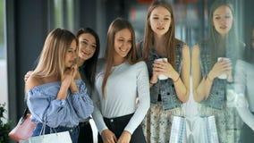 Vier gelukkige mooie vrouwen die en storefronts winkelen bekijken stock video