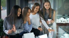Vier gelukkige mooie vrouwen die en storefronts winkelen bekijken stock videobeelden