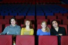 Vier gelukkige vrienden zitten op zetels in bioskooptheater Royalty-vrije Stock Foto