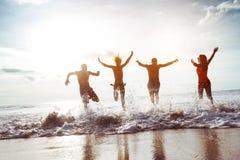 Vier gelukkige vriendenlooppas aan zonsondergangstrand stock foto