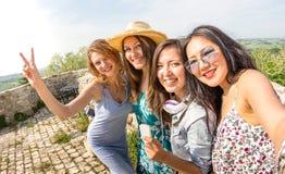 Vier gemischtrassige tausendjährige Freundinnen, die selfie an der Landseitenexkursion - glückliche Mädchen haben Spaß um alte St lizenzfreie stockfotografie