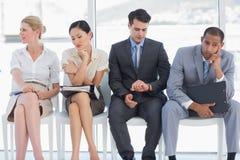 Vier Geschäftsleute, die auf Vorstellungsgespräch warten Stockbilder