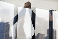 Vier Geschäftsleute, die zusammen mit den Händen auf der anderen Seite einer Glaswand stehen und zujubeln Stockfoto