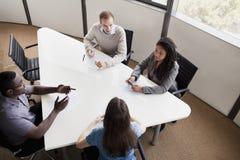Vier Geschäftsleute, die an einem Konferenztische sitzen und während eines Geschäftstreffens sich besprechen Lizenzfreie Stockfotografie
