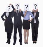 Vier Geschäftsleute, die Papier mit Fragezeichen, undeutlich gemachtes Gesicht, Atelieraufnahme halten Stockfotos