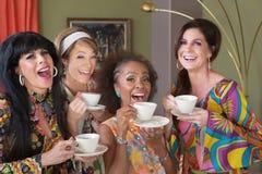 Vier glückliche Frauen, die Tee trinken stockfotografie