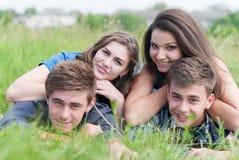 Vier glückliche Freunde, die zusammen draußen auf grünem Gras liegen Lizenzfreie Stockbilder