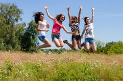 Vier glückliche Freundinnen der jungen Frauen, die hoch gegen blauen Himmel springen Stockbild