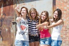Vier glückliche jugendlich Freunde, die sich Daumen zeigen Lizenzfreies Stockfoto