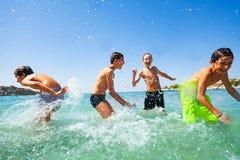 Vier glückliche Jungen, die am tropischen seichten Wasser spielen stockbilder