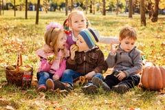 Vier glückliche Kinder, die im Park mit Früchten spielen lizenzfreies stockfoto