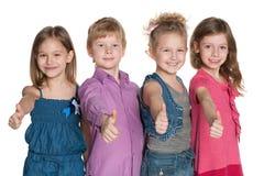 Vier glückliche Kinder halten seine Daumen hoch Stockbild