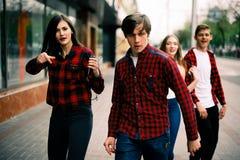 Vier glückliche modische Jugendfreunde, die in die Stadt, hörend Musik mit den Kopfhörern gehen und tanzen und sprechen sich und stockfoto